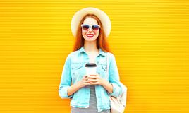 Happy stylish girl with coffee cup on a orange Royalty Free Stock Photos