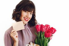 Happy stylish girl holding greeting card with space for text and. Pink tulips and gift box with ribbon and smiling on white background. happy mothers or womens Royalty Free Stock Images