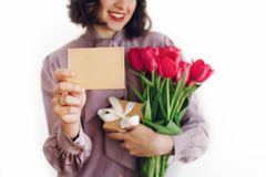 Happy stylish girl holding greeting card with space for text and. Pink tulips and gift box with ribbon and smiling on white background. happy mothers or womens Stock Images