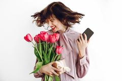 Happy stylish girl smiling and dancing with phone and holding pi. Nk tulips and gift box on white background. happy mothers or womens day concept. emotional Royalty Free Stock Photo