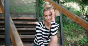 Happy stylish girl wearing denim jacket sitting on wooden stairs in a city park. Royalty Free Stock Images