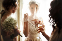 Happy stylish gorgeous blonde bride with bridesmaids on the bac. Kground  hotel room Royalty Free Stock Image