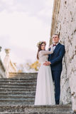 Happy stylish groom holding his pretty bride while both stand on antique stone stairs. Full length portrait.  Royalty Free Stock Image
