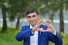 Happy stylish groom making a heart shape with hands Royalty Free Stock Photos