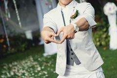 Happy stylish groom making a heart shape with hands. Groom in a bright suit with a white clock royalty free stock photos