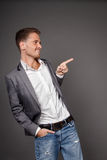 Happy stylish handsom man pointing space. On gray background Stock Image