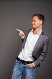 Happy stylish handsom man pointing space. Isolated on gray background Royalty Free Stock Images