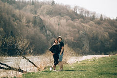 Happy stylish hipster couple hugging and smiling at mountain riv Royalty Free Stock Image