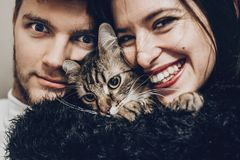 Happy stylish hipster family hugging with their cat. man and wom. Happy stylish hipster family hugging with their cat. men and women holding kitty and having fun Stock Images