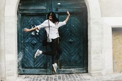 Happy stylish hipster woman jumping and having fun. On background of old wooden door at european street royalty free stock photography