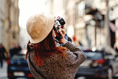 Happy and stylish hipster woman taking photo with film photo cam. Era on background of old building in european city Royalty Free Stock Photo