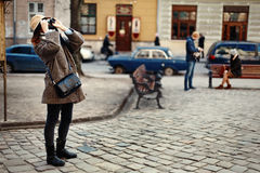 Happy and stylish hipster woman taking photo with film photo cam. Era on background of old building in european city Royalty Free Stock Images