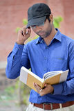Happy stylish indian young businessman reading book outdoor. This photo capture in kapshi in india Stock Photos