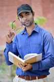 Happy stylish indian young businessman reading book outdoor. This photo capture in kapshi in india Stock Photography
