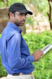 Happy stylish indian young businessman reading book outdoor Royalty Free Stock Photo