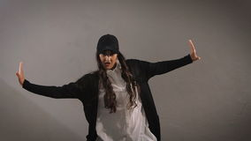 Happy stylish long-haired young woman in white shirt, black trousers, jacket and black cap is jumping and showing modern stock video