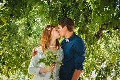 Happy stylish loving couple of hipsters hugging and kissing in a park royalty free stock image
