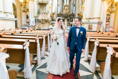 Happy stylish newlyweds walking holding hands in the church  on wedding ceremony Stock Photos
