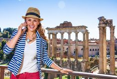 Happy stylish traveller woman in Rome, Italy using cell phone Royalty Free Stock Images