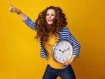 Happy stylish woman with clock pointing at something Stock Photos