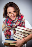 Happy stylish woman holding a pile of books. Happy stylish woman in a colorful winter scarf and eyeglasses holding a pile of hardcover books under her arm as she Royalty Free Stock Photography