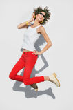 Happy stylish woman jumping with cell phone Royalty Free Stock Images