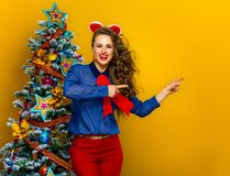 Happy stylish woman near Christmas tree pointing at something Royalty Free Stock Photos
