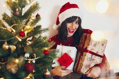 Happy stylish woman in santa hat holding many gift boxes with bo Royalty Free Stock Photos