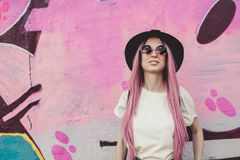 Happy stylish young hipster woman with long pink hair, hat and sunglasses on the street. royalty free stock images