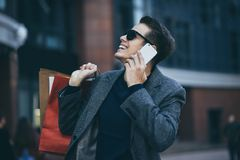 Happy stylish young man with phone walking in urban street and enjoying Black Friday shopping in trendy stores in city. royalty free stock photos