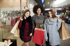 Happy stylish young multiethnic women with shopping bags walking in shopping mall with paper eco bags. Caucasian and Royalty Free Stock Images