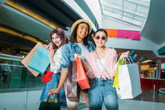 Happy stylish young women with shopping bags posing in shopping mall. Young girls shopping concept Royalty Free Stock Photography