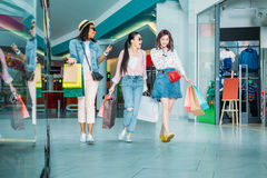 Happy stylish young women with shopping bags walking in shopping mall Royalty Free Stock Photo