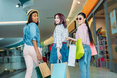 Happy stylish young women with shopping bags walking in shopping mall. Young girls shopping concept Royalty Free Stock Photos