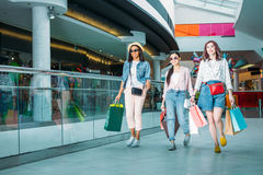 Happy stylish young women with shopping bags walking in shopping mall. Young girls shopping concept Stock Photography