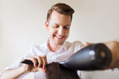 Happy stylist with fan making blow-dry at salon Stock Images