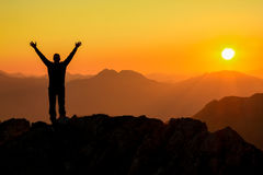 Happy success winning man arms up on mountain at sunset. Happy celebrating winning success man at sunset or sunrise standing elated with arms raised up above his Stock Photo