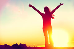 Happy success winning woman arms up at sunset. Happy celebrating winning success woman at sunset or sunrise standing elated with arms raised up above her head in Royalty Free Stock Photos