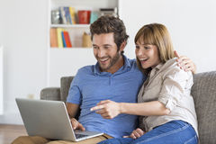 Happy success young couple with laptop on sofa in modern white apartment Stock Images