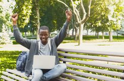 Happy successful african-american student with arms raised in the air. Young casual student with laptop celebrating victory outdoors. Winner and achievement Stock Images