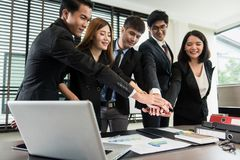 Happy successful Asian business team. Asian businessmen are working on a big project. And overlapping hands to work together,,Focus is on hands stock photography