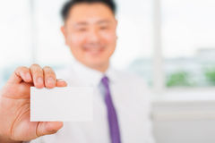 Happy and successful asian businessman gives you a business card Royalty Free Stock Photo