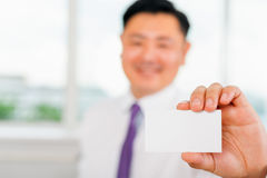 Happy and successful asian businessman gives you a business card Stock Images