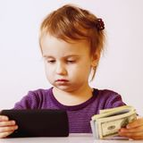 Happy successful business child girl holding a smartphone in fro. Nt of bunch of money humorous picture royalty free stock photography