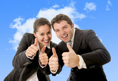 Happy successful business Hispanic woman and Caucasian man wearing suits giving thumbs up smiling on blue sky Royalty Free Stock Photo