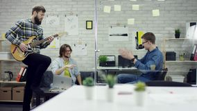 Happy successful business people in office having fun throwing documents. One worker is playing the guiter. They are stock footage