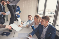 Happy successful business people in office having fun throwing documents Royalty Free Stock Photography