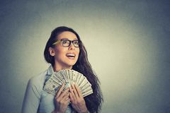 Happy successful business woman holding money dollar bills. Closeup portrait happy excited successful young business woman holding money dollar bills in hand Royalty Free Stock Image