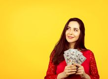 Happy successful business woman holding money dollar bills in hand. Happy successful young business woman holding money dollar bills in hand daydreaming lookin stock image