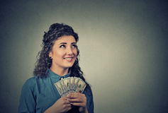 Happy successful business woman holding money dollar bills in hand looking up Stock Image